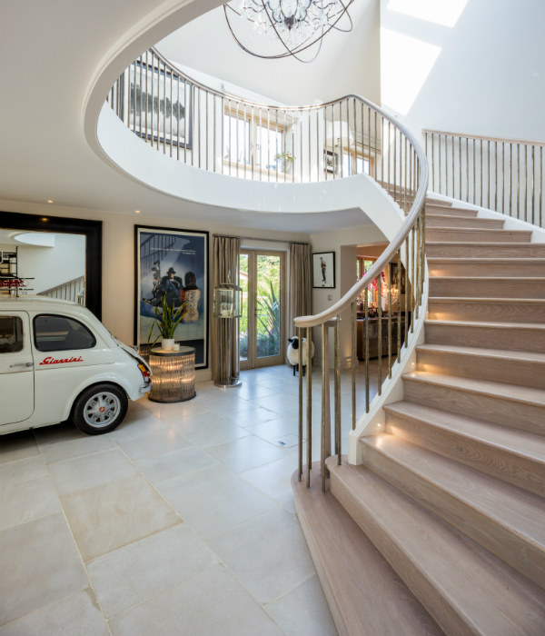 Grand hallway with spiral staircase and classic fiat car