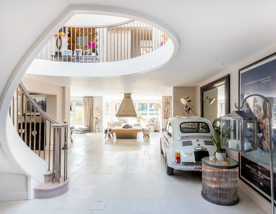 Grand open plan living space with spiral staircase, classic fiat, open fire and Lulworth stone flooring