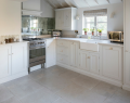 Cottage kitchen with cream cupboards and limestone flooring