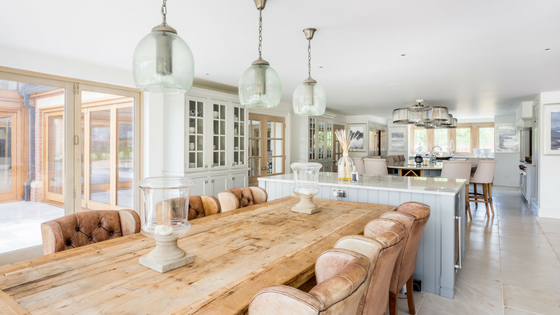 Open plan kitchen and dining space with long wood table